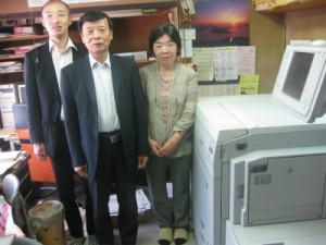 カラー出力ではキヤノンimagePRESS C700(右)が活躍。左から萬谷元宏氏、萬谷社長、萬谷峰子氏