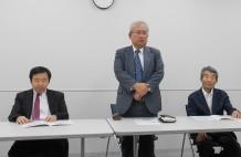 100周年事業についてあいさつする同窓会会長の湯本氏。(左:軍事幹事、右:五百旗頭顧問)