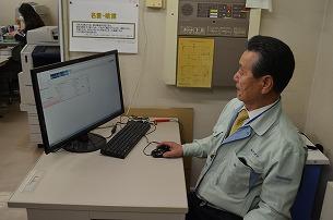 中綴じラインの生産状況を確認する永井社長