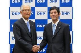 握手を交わす大日本印刷の北島義俊社長(左)と北島義斉次期社長