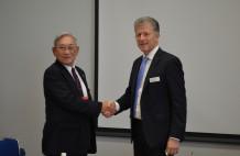 握手を交わす第一印刷所の堀一社長(左)、ミューラー・マルティグループCEOのブルーノ・ミューラー氏