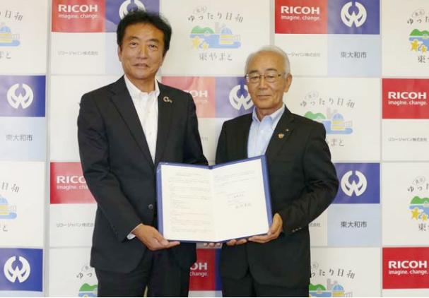 リコージャパン西東京支社長 鈴木太志氏(左)と東大和市 尾崎保夫市長