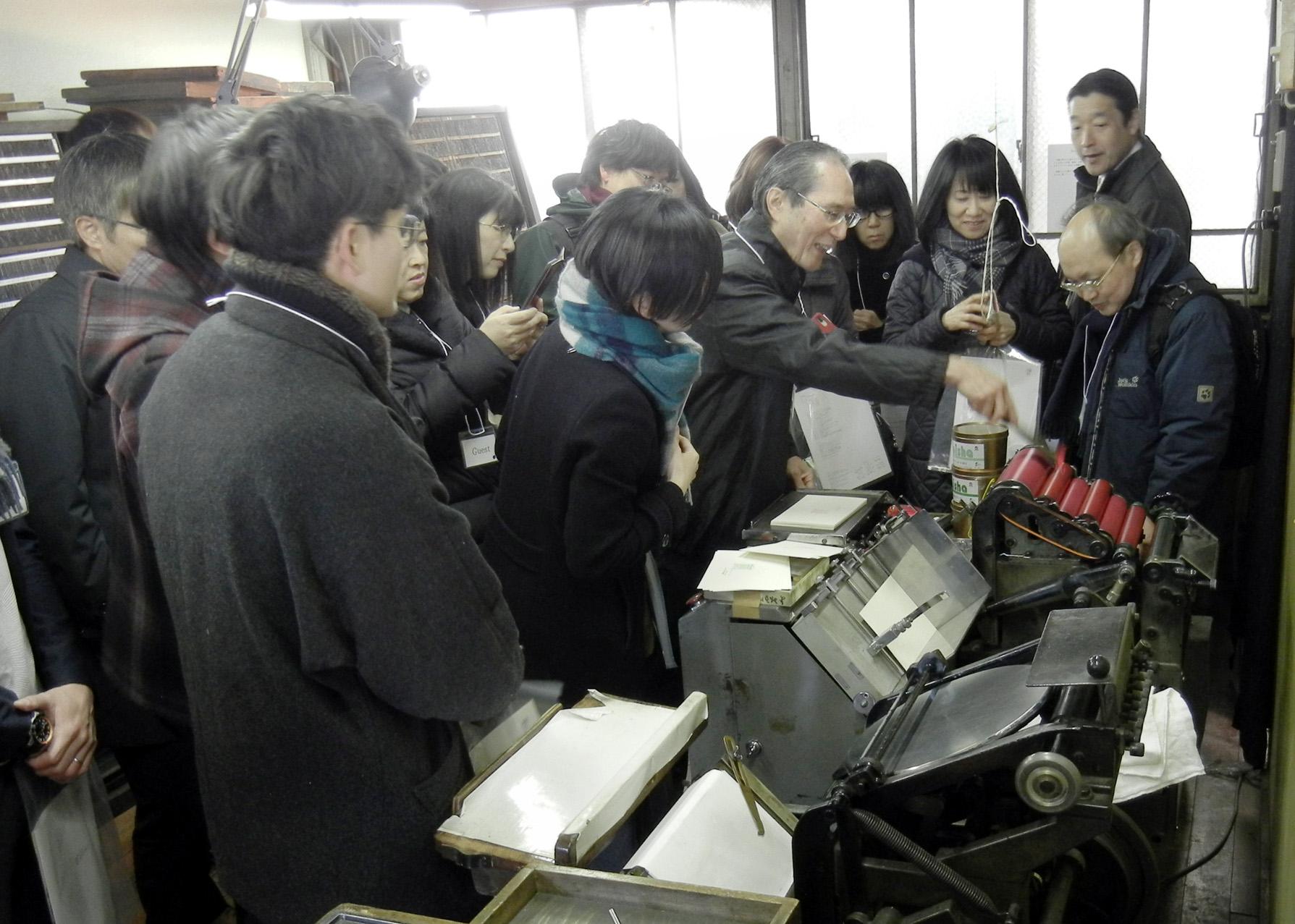 活版印刷に興味津々のお披露目会出席者。(櫻井印刷所の「活版印刷お披露目会」で)