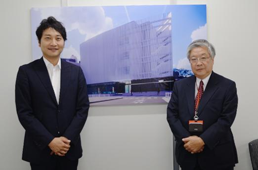 水上光啓会長(右)と河合克也社長(新社屋イメージ図の前で)