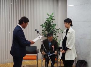 千修・下谷社長から賞状と副賞を受け取るリ ジャスミンさん(右)