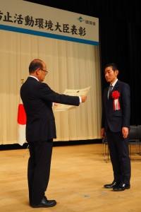 環境省大臣政務官の八木氏から表彰状を受け取る日本WPAの田畠会長