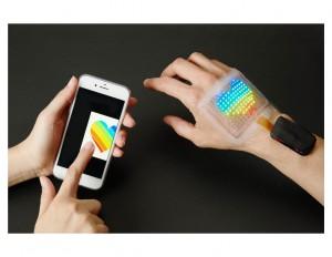 表示部と、駆動回路、BLE(Bluetooth Low Energy)通信回路、電源を一体化して皮膚に貼り付けられたフルカラースキンディスプレイ。