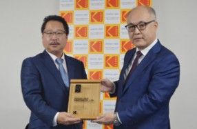 コダックジャパンの藤原社長(右)から記念の盾が贈られる千修岩井印刷の岩井社長