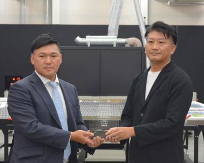 日本アグフア・ゲバルトの岡本社長(左)から記念の盾が贈られるキングプリンティングの光弘専務